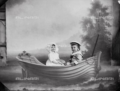 tca-f-000603-0000 - Anna ed Antonio Trombetta jr.  in abito elegante su una barchetta (scenario di studio) - Data dello scatto: 1910 ca. - Archivi Alinari-donazione Trombetta, Firenze