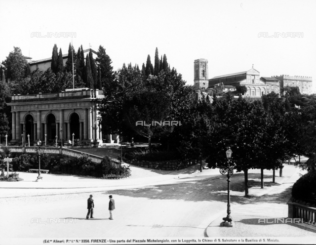 Partial view of Piazzale Michelangelo. The gallery, the Church or San Salvatore and the Basilica of San Miniato are in the background. Two men are chatting on the street.