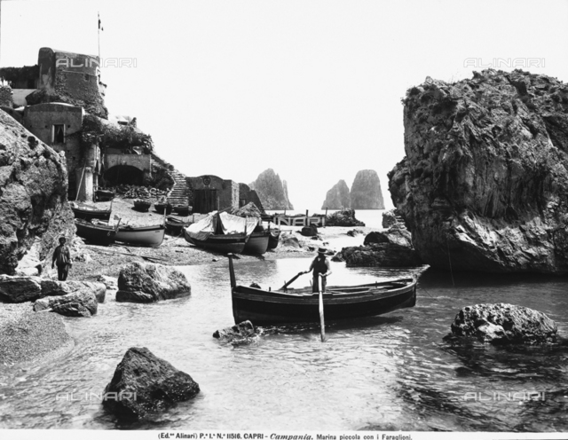 Rocks at the Marina Piccola of Capri. A man docking his boat is in the foreground