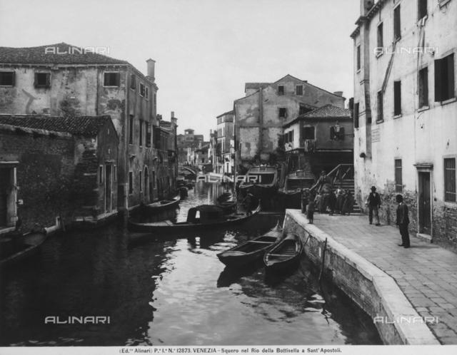 View with people of Rio della Bottisella near Piazza dei Santi Apostoli, in Venice