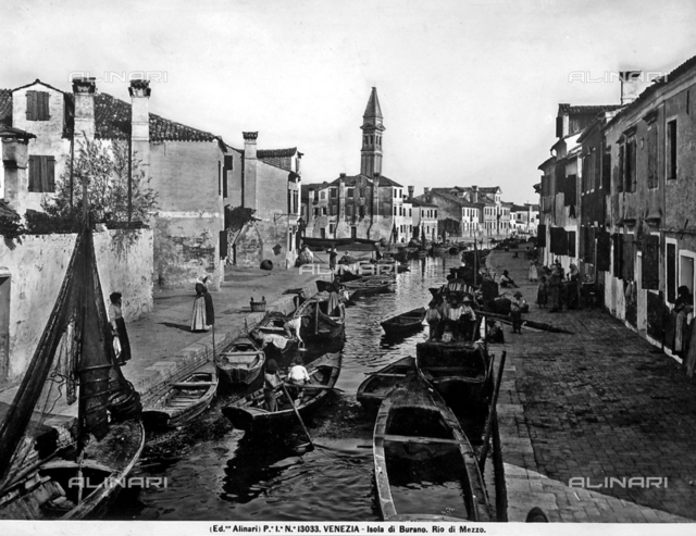 View of Rio di Mezzo on the island of Burano in the Venice lagoon. View of moored boats, houses and some people on the bank.