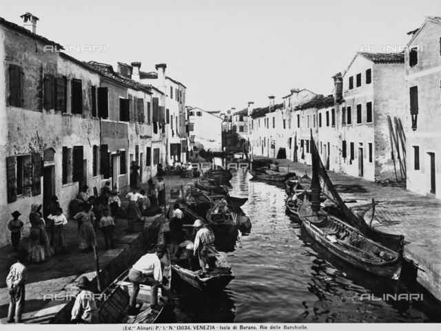 A group of people along the Rio delle Burchielle on the island of Burano, near Venice