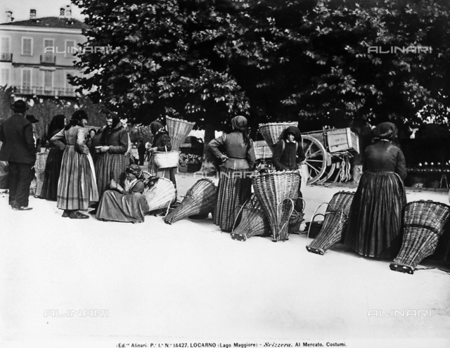 Women in traditional costume next to wicker chests at a market in Lucerne.