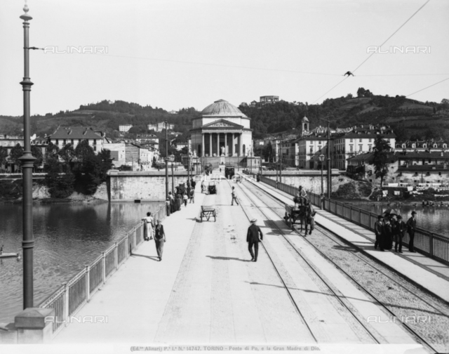 View of the Vittorio Emanuele I Bridge or of the Po River, in Turin. In the background the Gran Madre di Dio is visible. It is a neo-classic structure with hexastyle pronao and circular ceiling. Some passers-by and a horse carrying a cart are visible on the bridge