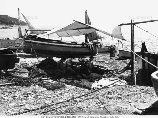 Fishermen at the marina near Cogoleto on the Riviera of Genoa. Some fishermen emptying fishing baskets and nets are visible in the foreground.