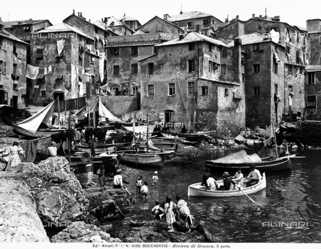 Busy panoramic view of the port of Boccadasse with boats in the sea. Children are playing on the rocks.