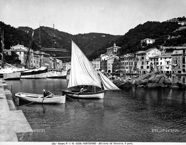 The small port of Portofino, with moored sailboats. In foreground are some row boats.