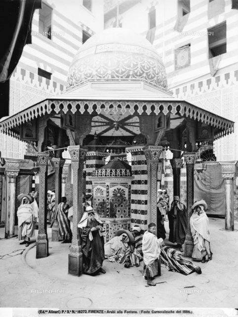 Men dressed as Arabs, seen near a fountain decorated for the Carnival festivities held in Florence in 1886