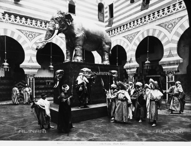 Men dressed as Arabs, seen near a statue of an elephant, during the Carnival festivities held in Florence in 1886