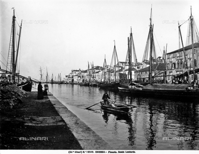 View of the Lombardo Canal in Chioggia. Many sailboats can be seen along the canal; in the center, there is a man rowing a small rowboat