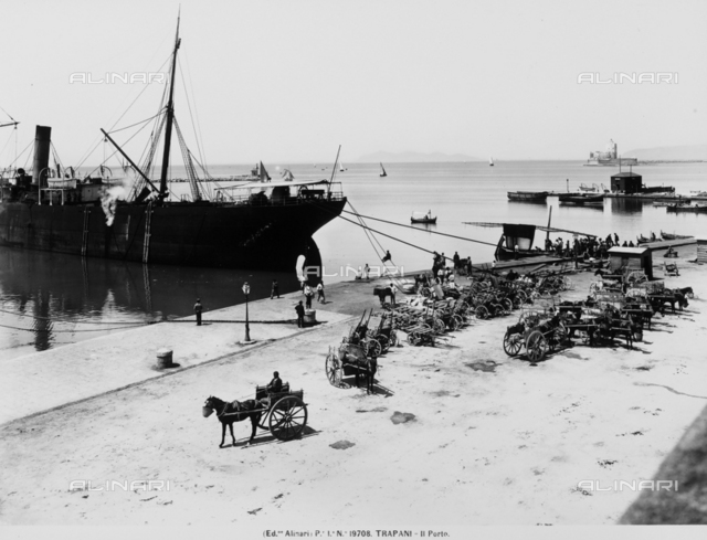The pier at Trapani with a moored ship and several parked carts