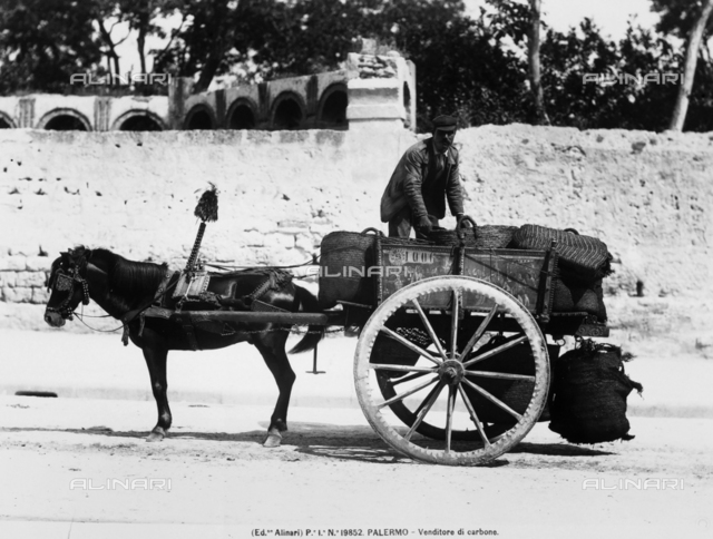 Coal vendor photographed in his cart full of straw bags. The cart is pulled by a small horse.