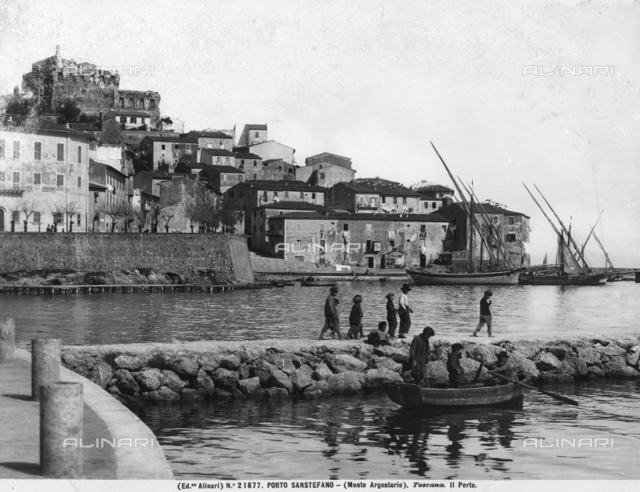 View of Porto Santo Stefano. Section of the port with some boats and a group of children on the pier