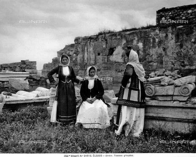 Portrait of three young women dressed in traditional costume, Eleusi. The ruins of old buildings are visible in the background.