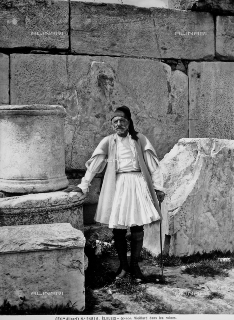 Portrait of an elderly man dressed in traditional costume, Eleusis. Next him are the remains of some old buildings.