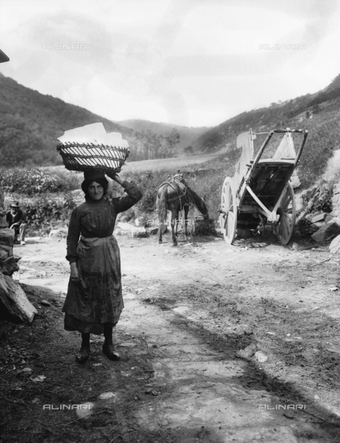 A female ice worker of Maladrone, on the Pistoian Apennines, carrying a large block of ice on her head. On the right is a horse and cart