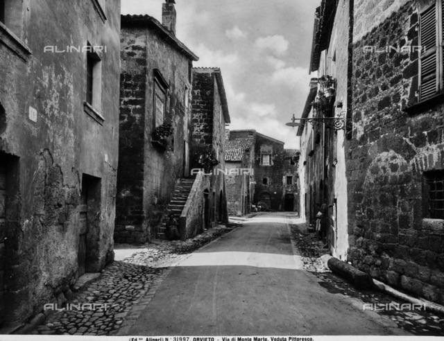 View of Via Monte Marte, Orvieto. Stone houses with flower vases in the windows are visible on the sides