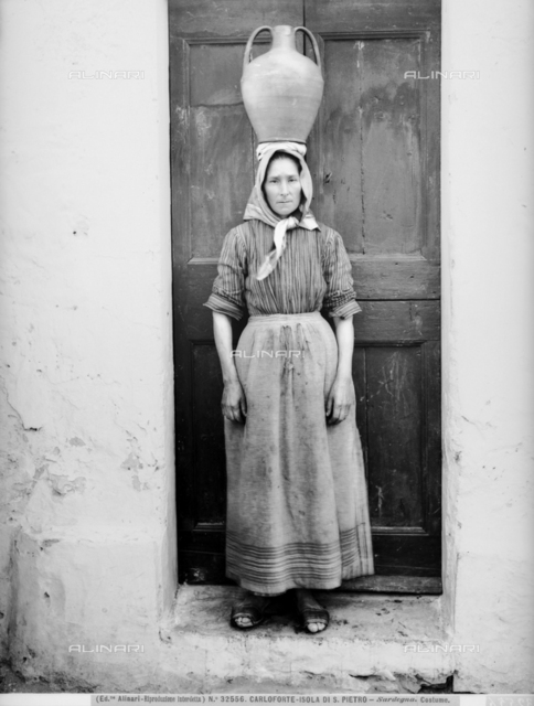 Woman in traditional dress, photographed in front of the door of a house, while carrying an amphora on her head, Carloforte, Island of San Pietro.