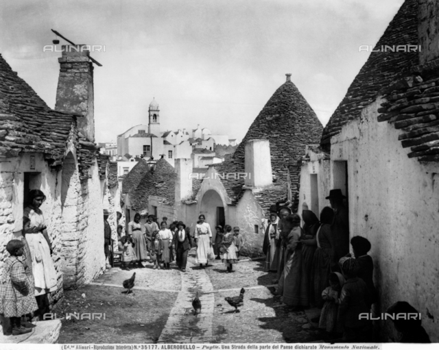 View of a busy street with cylindrical houses with conical roofs, Alberobello.