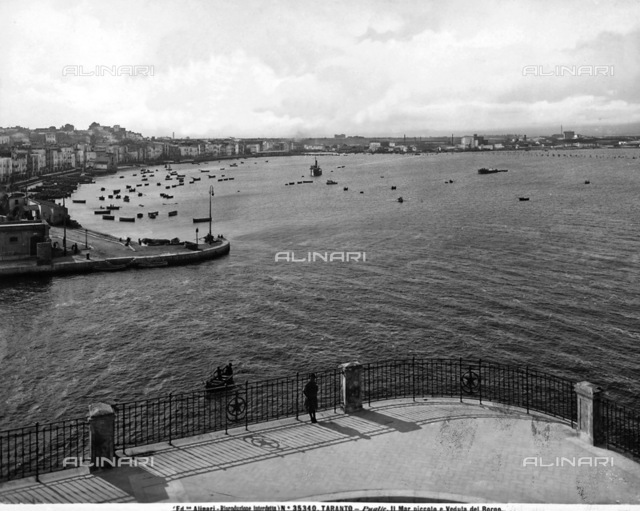 Panoramic view of porto di Taranto; in the background some industrial establishments are visible, on the left are moored boats and a view of the city, in the foreground, a woman is leaning on the railing of piazzale, observing the view
