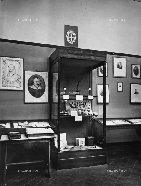 View of a room with some portraits hung on the walls, some books and other objects belonging to the University of Pavia. In the central glass case are some mounted animals, by Professor of Anthropology, Paolo Mantegazza, between 1862 and 1866, prepared by Rusconi. In the center is an exhibit on the galvanoplasty in 1800-1802 of doctor and chemist Luigi Brugnatelli. Some devices of Bottini are visible below. The photo was taken on the occasion of the Exhibition on the History of Science held in F