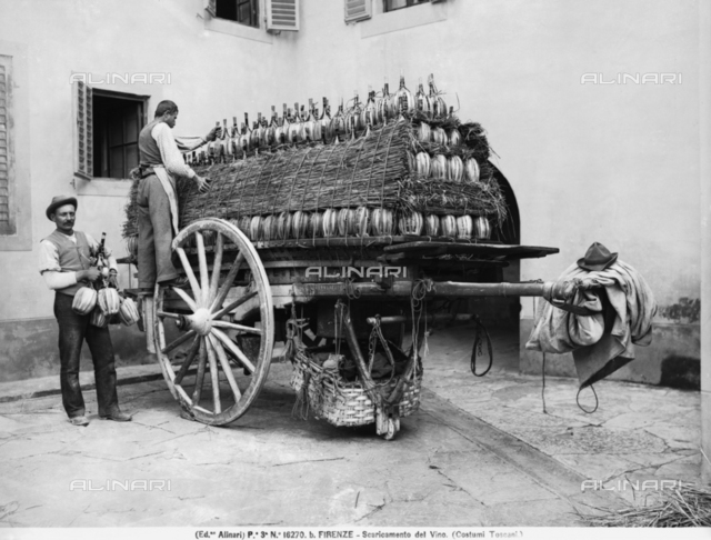 Men unloading flasks of wine from a cart