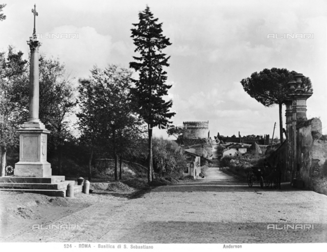 View of Via Appia and the entrance to the San Sebastiano Catacombs and the commemorative column. The Tomb of Cecilia Metella can be seen in the distance