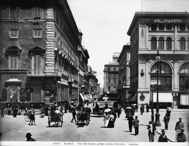 "View of Via del Corso in Piazza Colonna in Rome: the street is crowded with carriages and passersby. On the right, the palace of ""Rinascente"""