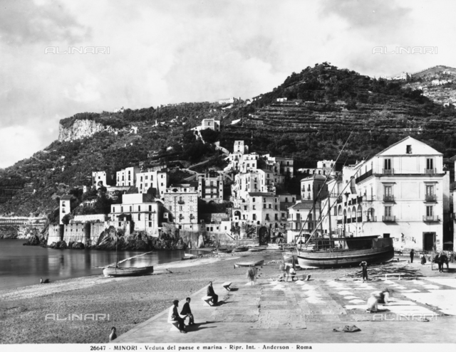 Panoramic view of Minori, a town on the Amalfi Coast, with houses perched on the hill slopes and beached boats in the small port
