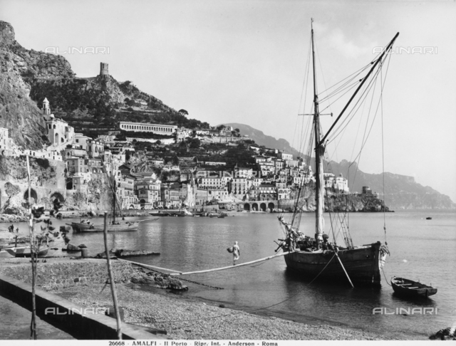 Panoramic view of Amalfi with the port in the foreground and a sailor about to get on a moored sailboat