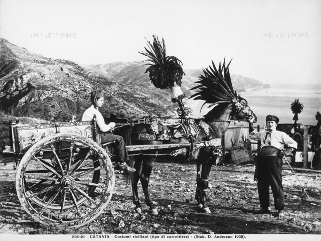 Sicilian cart driven by two carters, dressed in traditional costume. In the background, the coast of Catania is visible.
