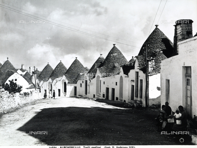 View with people of cylindrical houses with conical roofs, Alberobello.