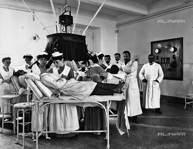Patients in hospital beds in the phototherapy department of the Pellizzari Institute of Florence.