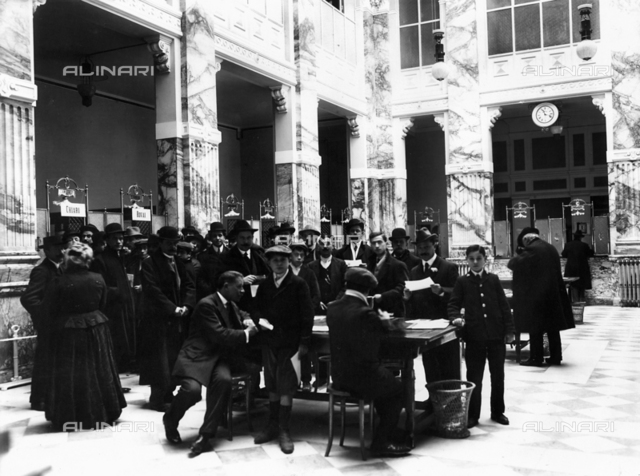 A large group of people crowd around the bank counters of the Credito Italiano Bank, in Florence