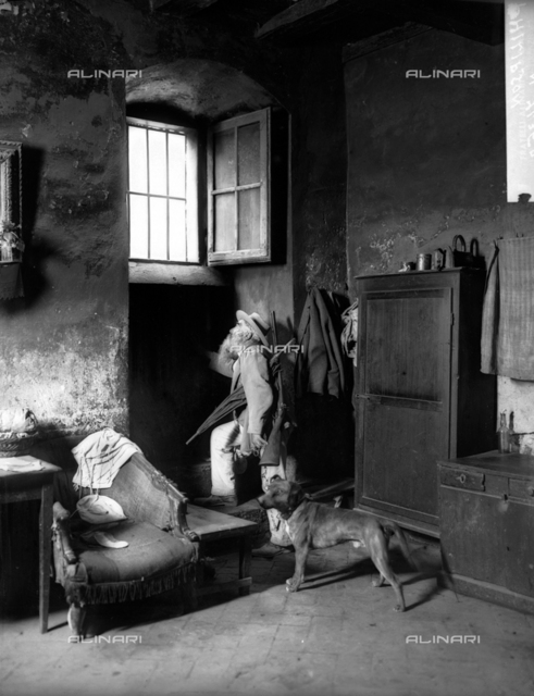 """Portrait of the """"hunter"""" with his dog inside a house."""