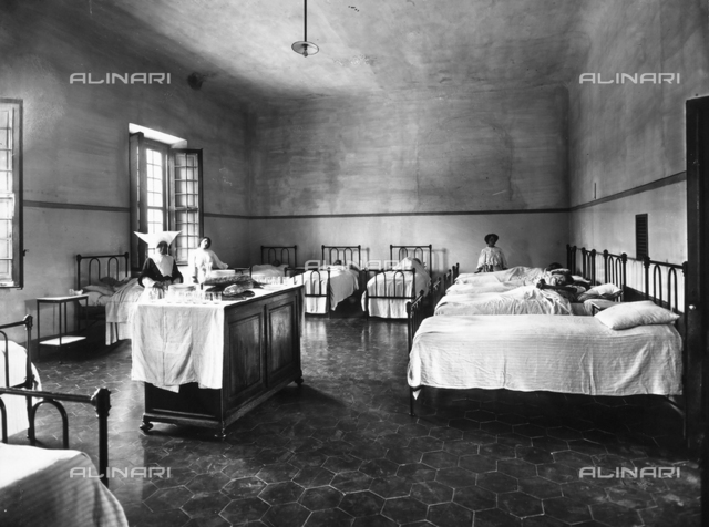 A dormitory in the Psychiatric Hospital of San Salvi, in Florence; some patients in bed