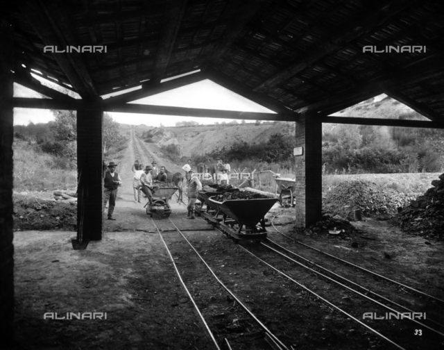 Group of miners shown near carts carrying coal, in the Moriani di Follonica mine.