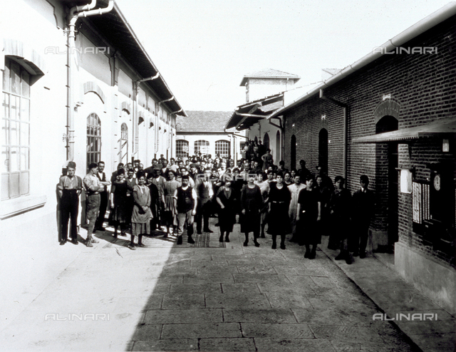 Group portrait of the employees of the Conceria Pedani, standing. Half of them are in the shade. In the courtyard, on the right, on the wall the clock for punching in