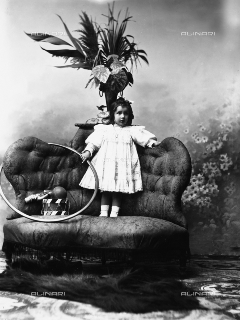 Portrait in studio of child standing on sofa