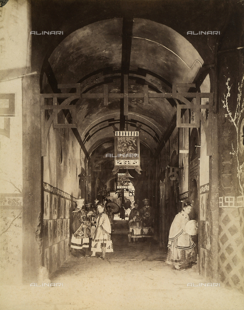 Carnival celebrations in the Florentine ghetto, 1888. Men and women, dressed in folkloristic costumes, strolling down a Florentine alley