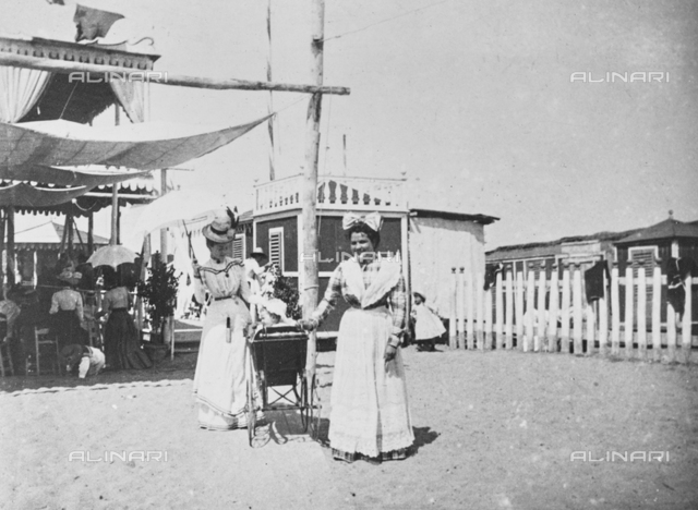 Young lady with a baby in pram and nursery on the beach of Viareggio