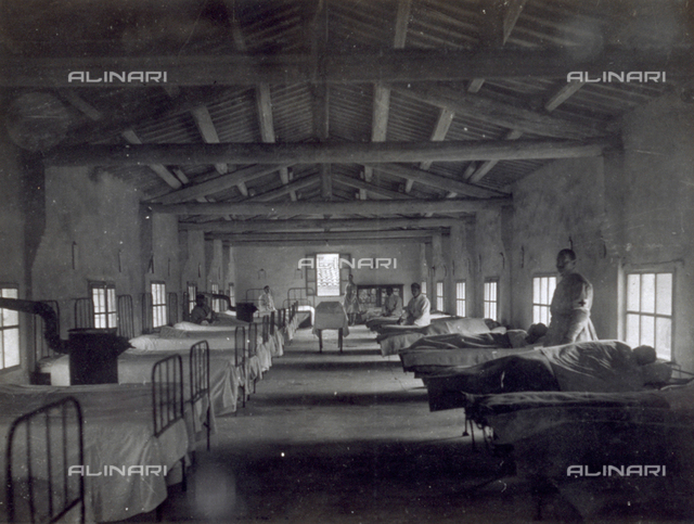 Main room of an infirmary in Noventa Vicentina. The large room, with an open timber roof, contains two rows of beds. A few patients and two red cross nurses are visible