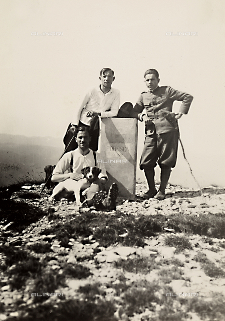 Three men and a dog photographed near a boundary stone, on top of Monte Porozen, at the Italian-Slovenian border.