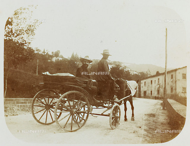 Two men on a horse-drawn carriage along a road; postcard