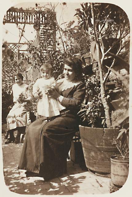Two women with a child photographed in a terrace; postcard