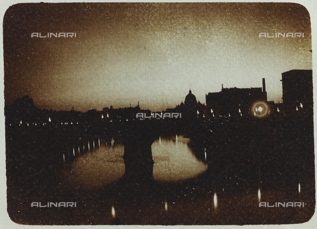 Night view of Rome with the Sant'Angelo bridge and the dome of the Basilica of San Pietro; postcard