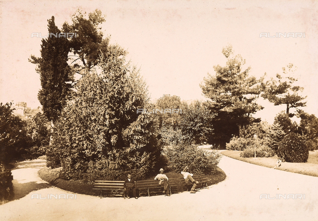 """The garden of """"La Villa"""" in the city of Teramo. In the foreground, two men and a small boy are seated on benches."""