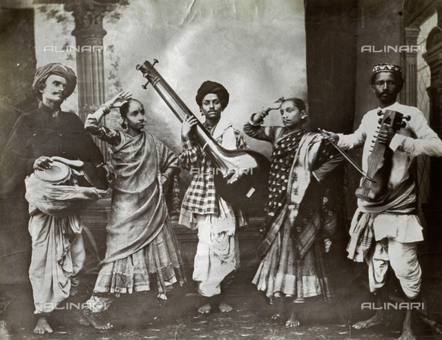 Studio portrait of a group of musicians and women dancers from the Island of Ceylon, in ethnic clothes