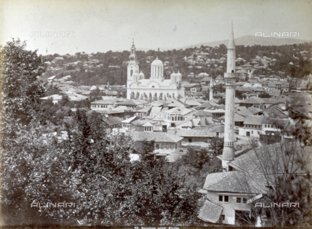 Panorama of Sarajevo, taken along the Brod-Sarajevo section of the railway line. At the center an agglomorate of houses interpose from the vegetation, the side of a large Greek church can be identified. In the foreground tree branches and a minaret