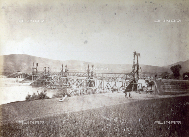 Image of the bridge of Zenica, along the Brod-Sarajevo railway line, on the day of its inauguration. Beyond a field in the foreground, the metallic bridge spanning the river, supported by wooden structures, and decorated with flags and plants. A few men pause on the bridge.